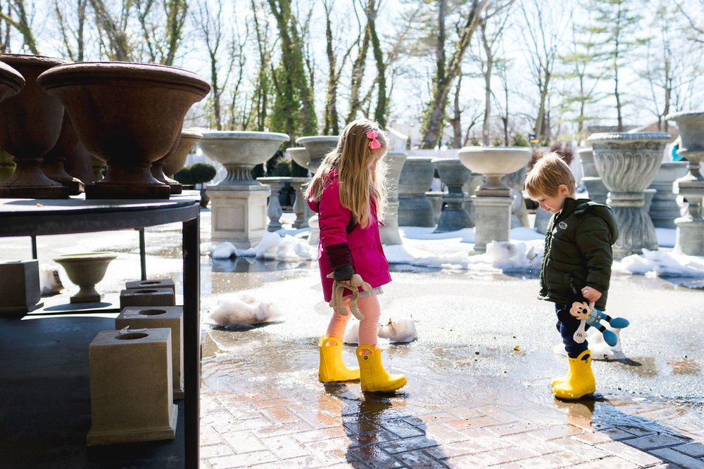 Boy and girl splash in puddles at Hicks Nursery.