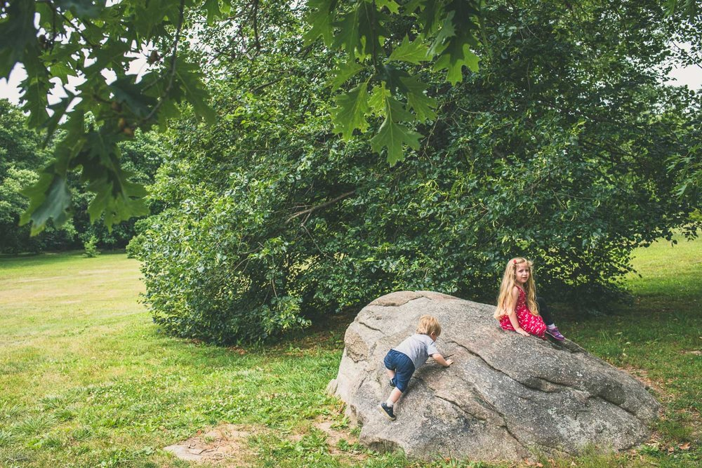 Children climbing rocks at Planting Fields Arboretum in Oyster Bay.