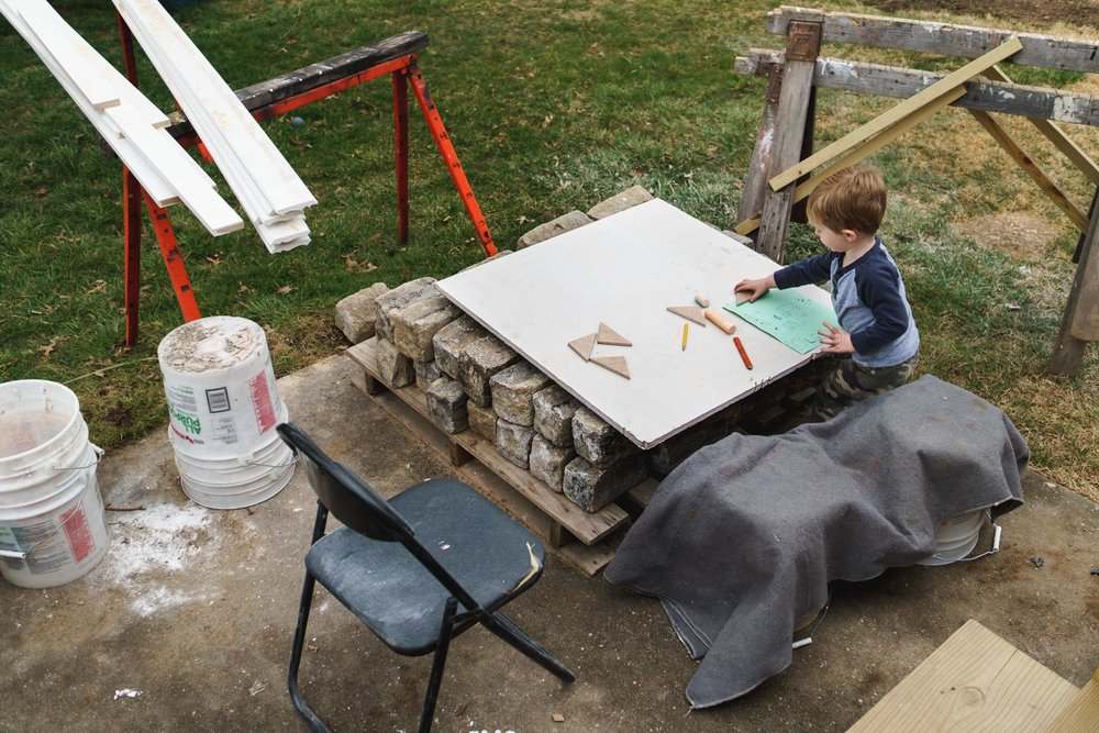 Little boy draws on a piece of sheet rock in the backyard.