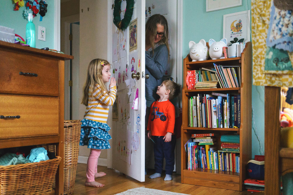 Woman playing hide-and-seek with two small children.