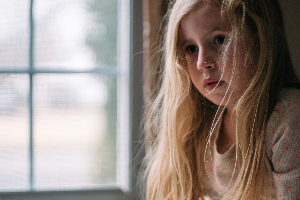 Portrait of a little girl with blonde hair next to a window.