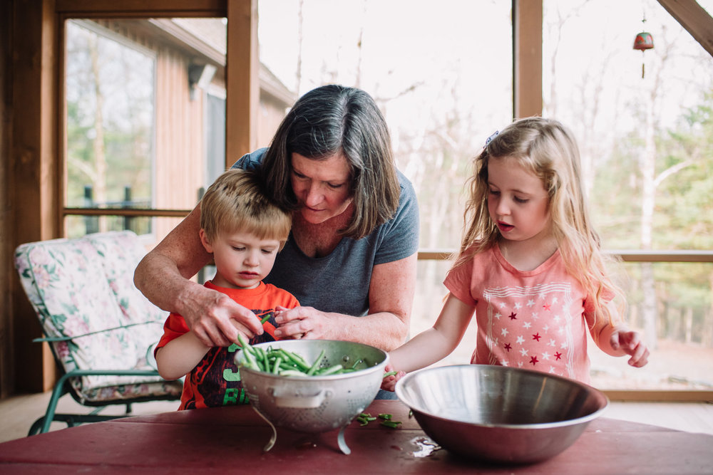 Grandmother shows children how to trim green beans