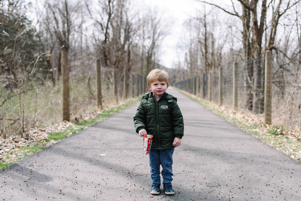 Little boy standing in the middle of a path surrounded by trees.