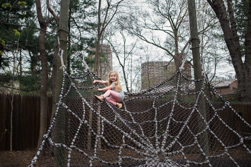 Little girl climbing a rope spider web at the Bronx Zoo.