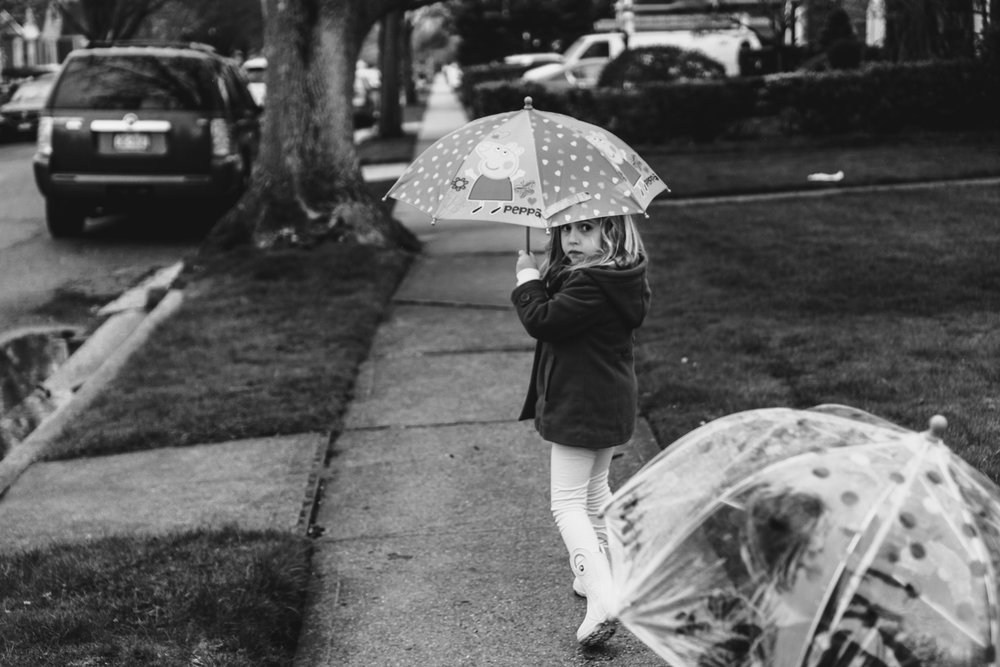 Kids walking in the rain with umbrellas.
