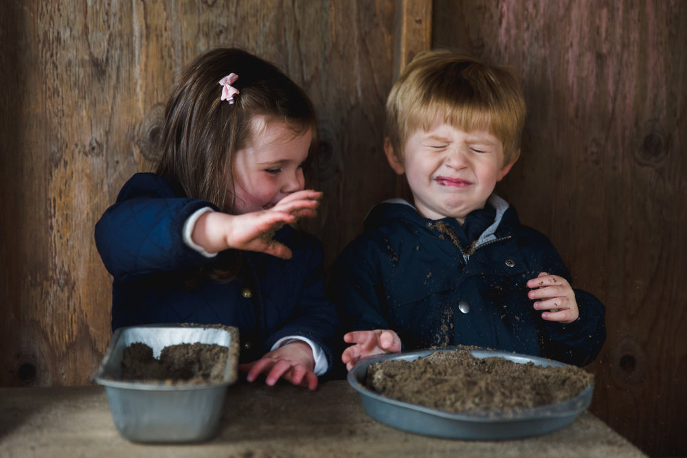 Little girl throwing sand in boy's face.