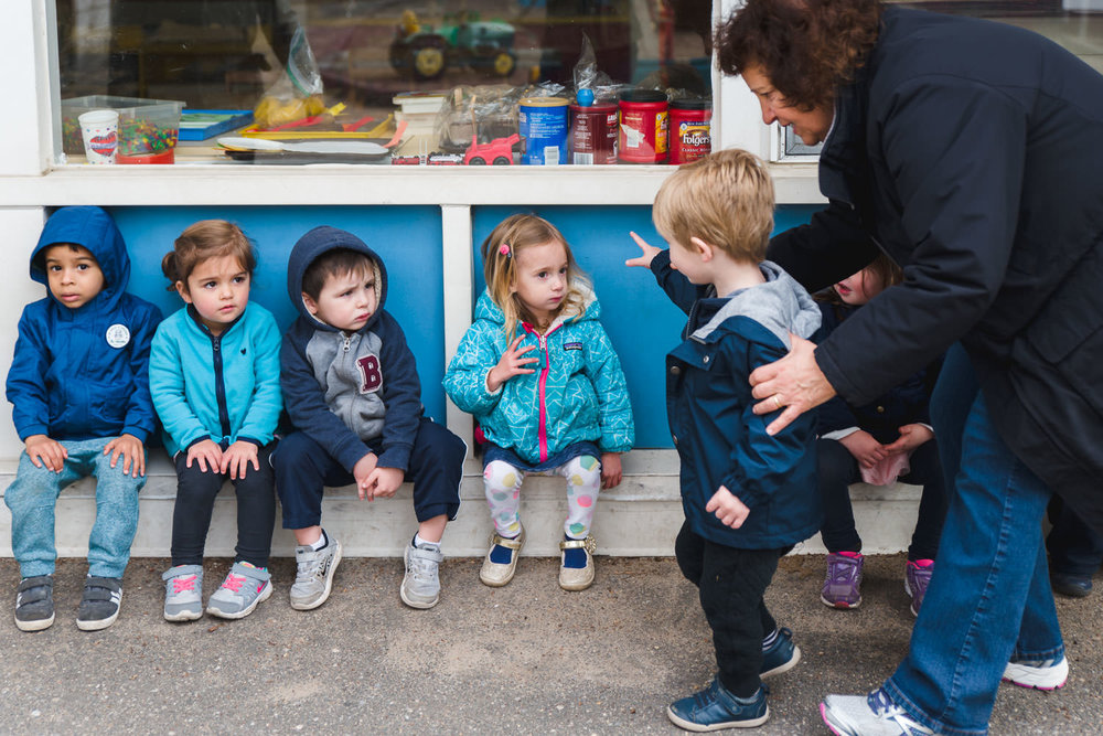Kids sitting in line while little boy counts attendance.