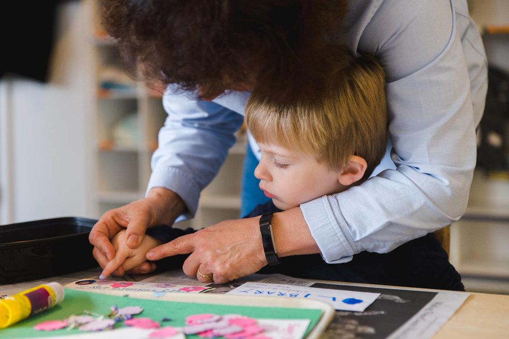 Teacher helps little boy with art project.