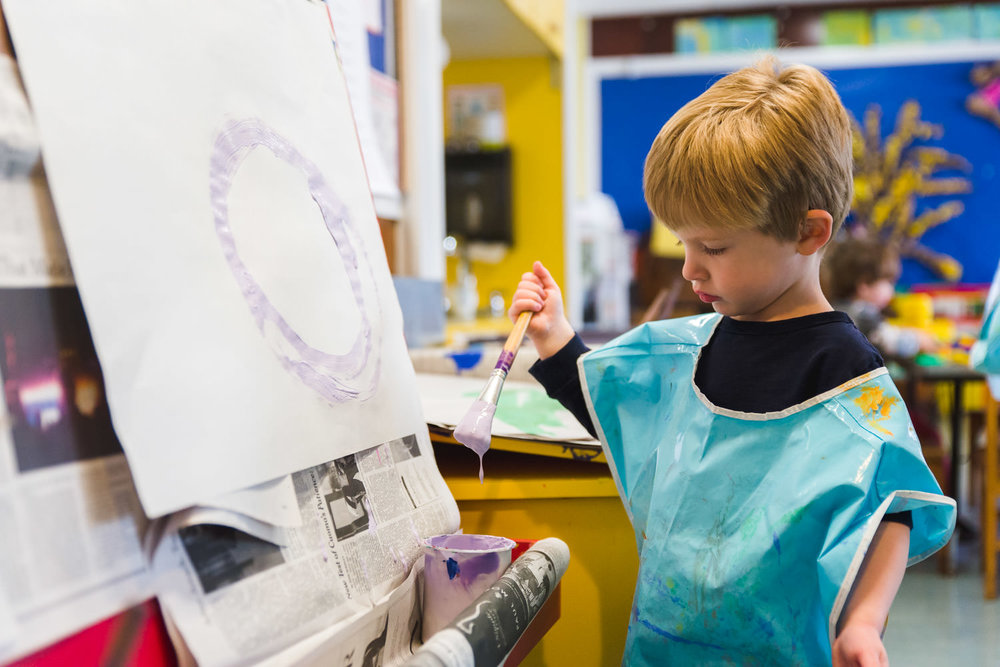Little boy painting at school.