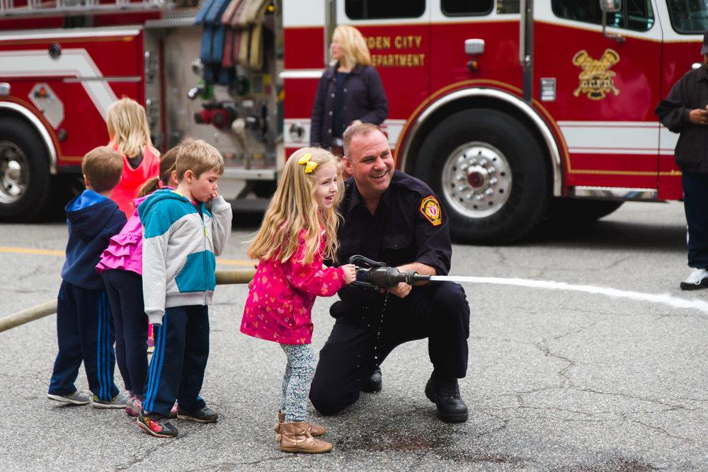 Little girl firing off firehose.