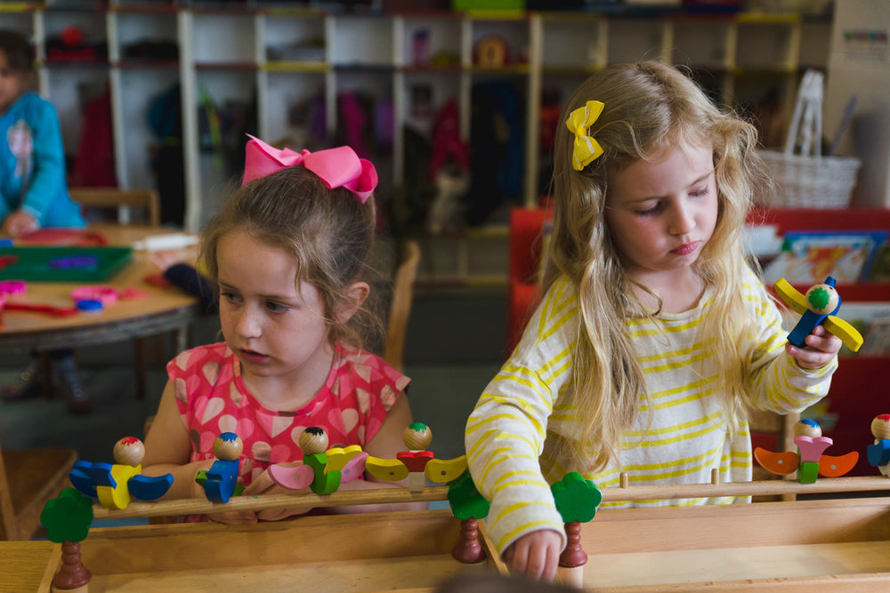Little girls playing with puzzles at school.