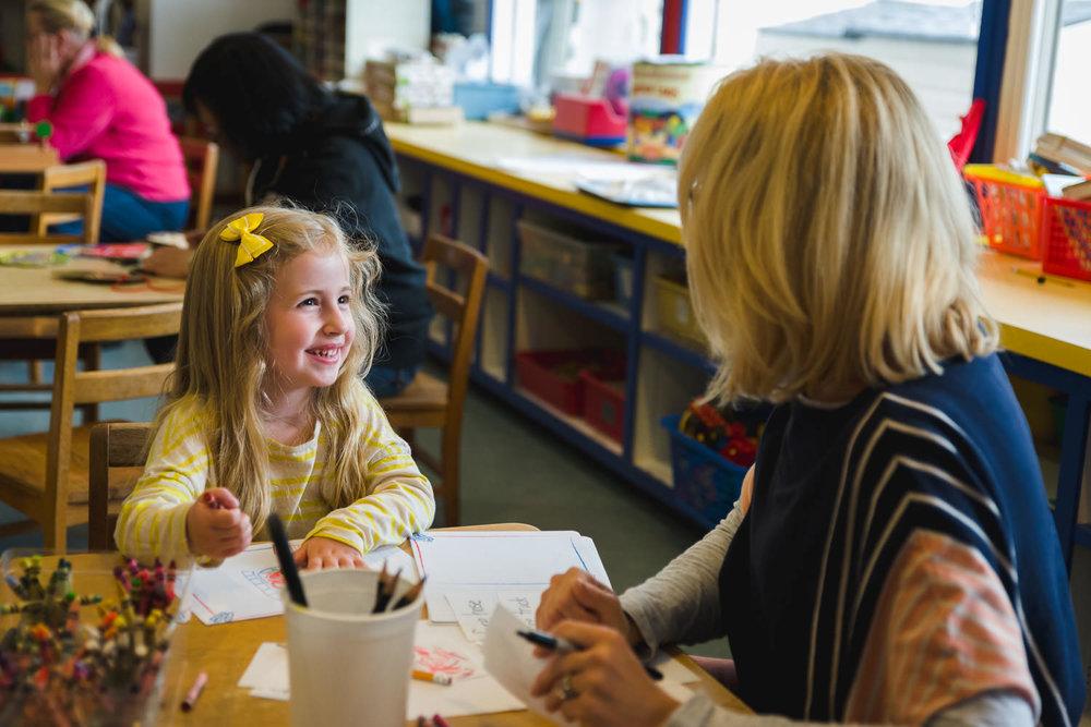 Little girl smiling at her teacher.