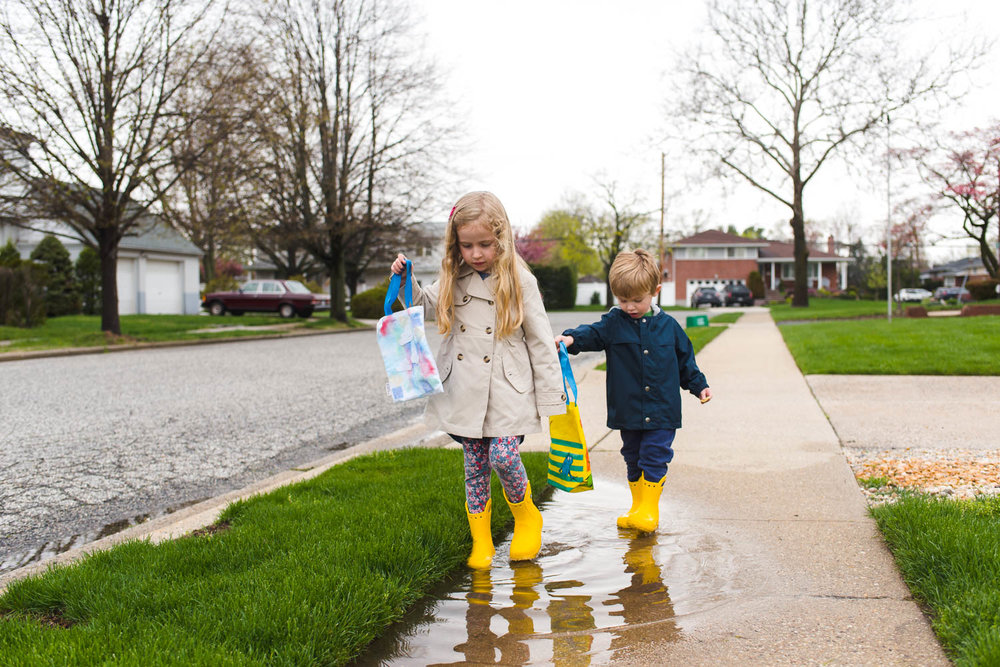 Kids walking through a puddle in yellow rain boots.