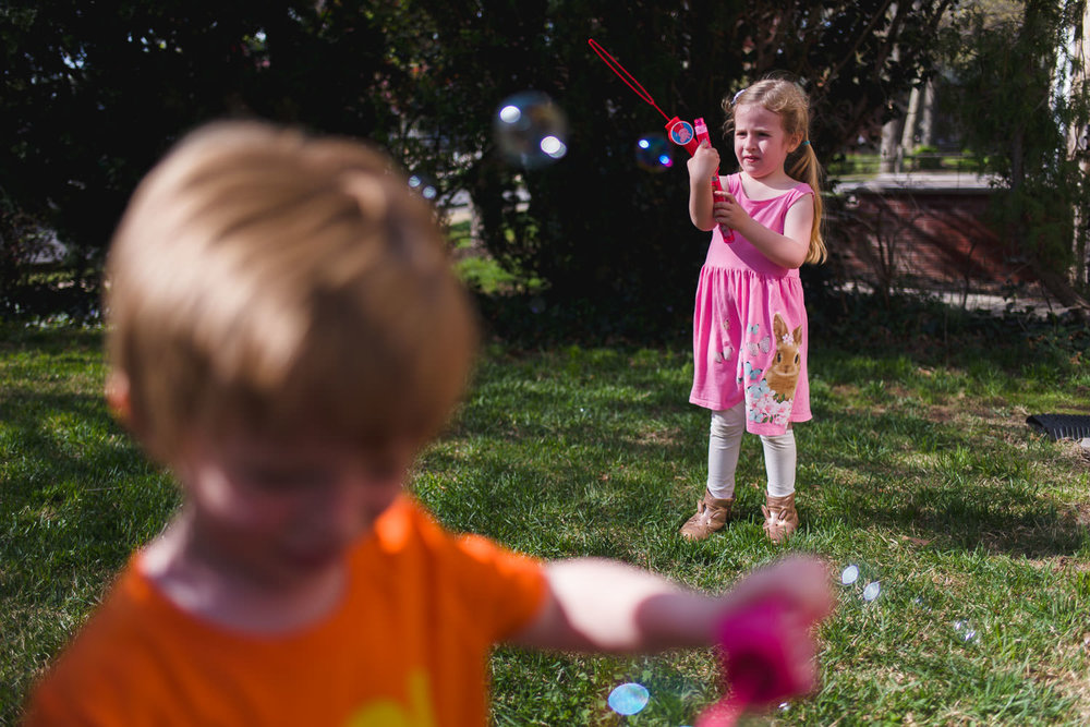 Boy and girl playing with bubbles on front lawn.