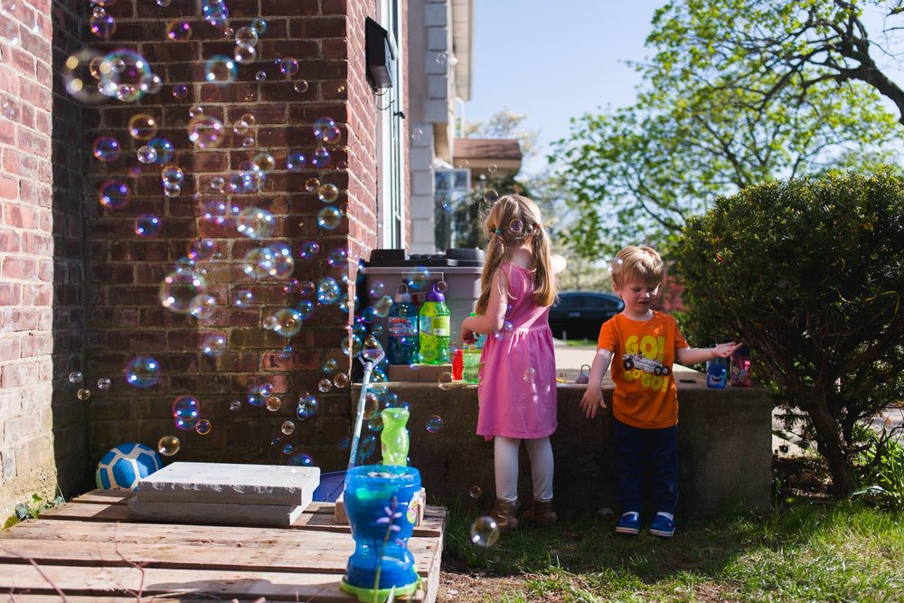 Kids in front yard with bubble machine.