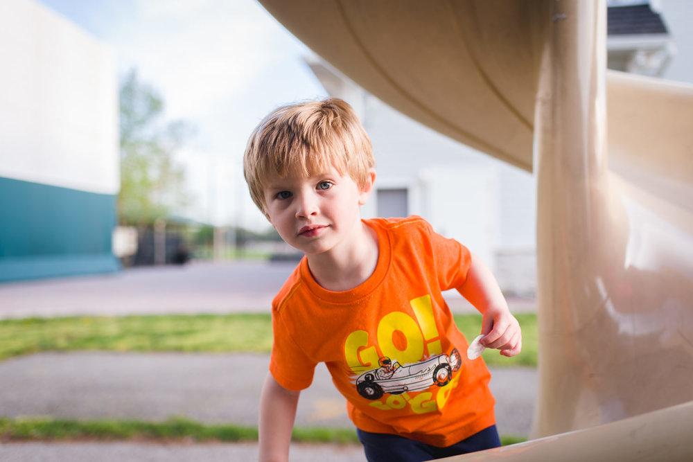 Little boy climbing up a twisty slide.