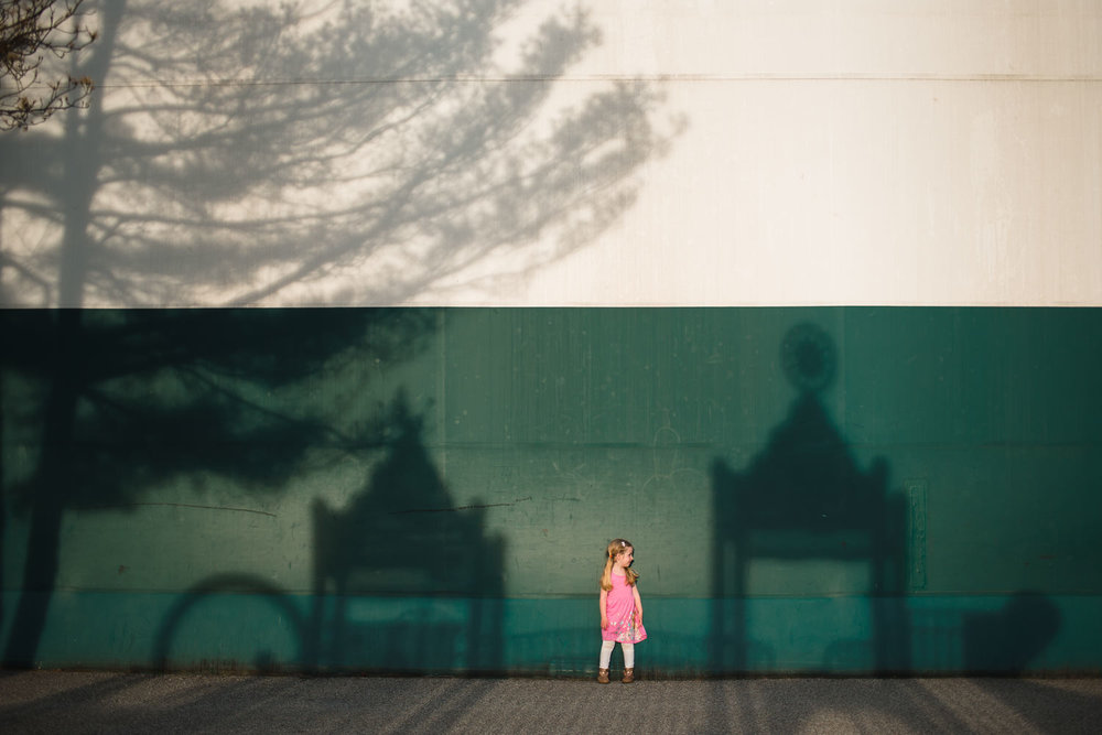 Little girl stands between two shadows of a playground structure.