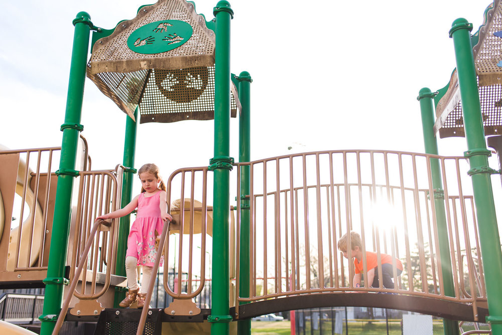 Kids play on a playground structure as the sun starts to go down.