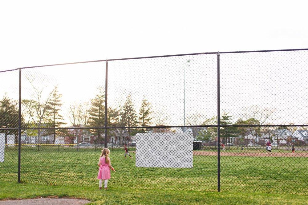 Little girl watches a baseball game.
