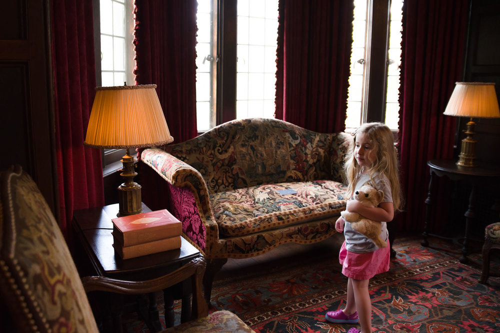 A little girl explores Coe House at Planting Fields Arboretum.