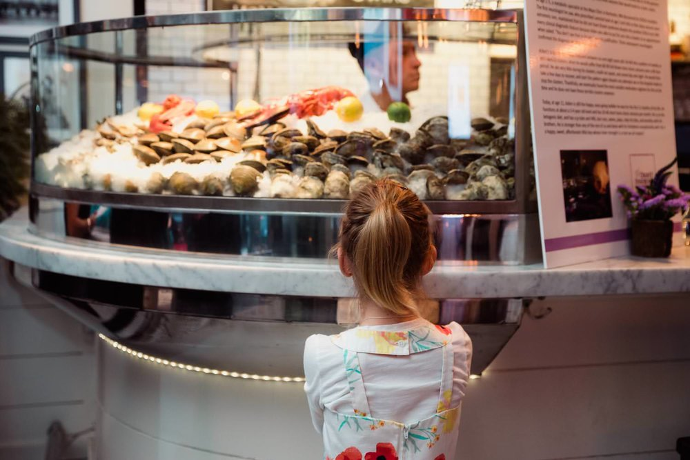A little girl looks at the seafood display at the Farmer and the Fish.