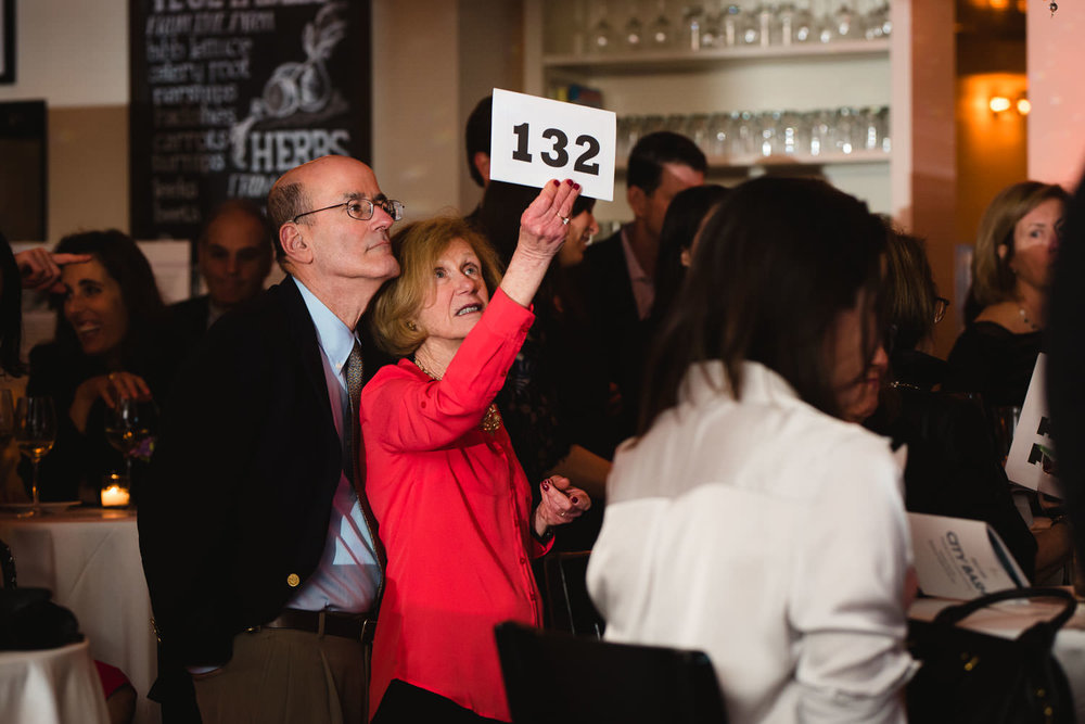 A woman bids on an auction prize.