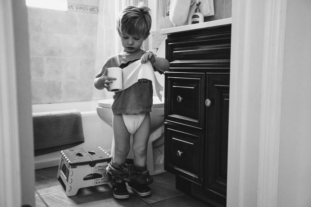 A little boy in the bathroom with diaper on, ripping toilet paper.
