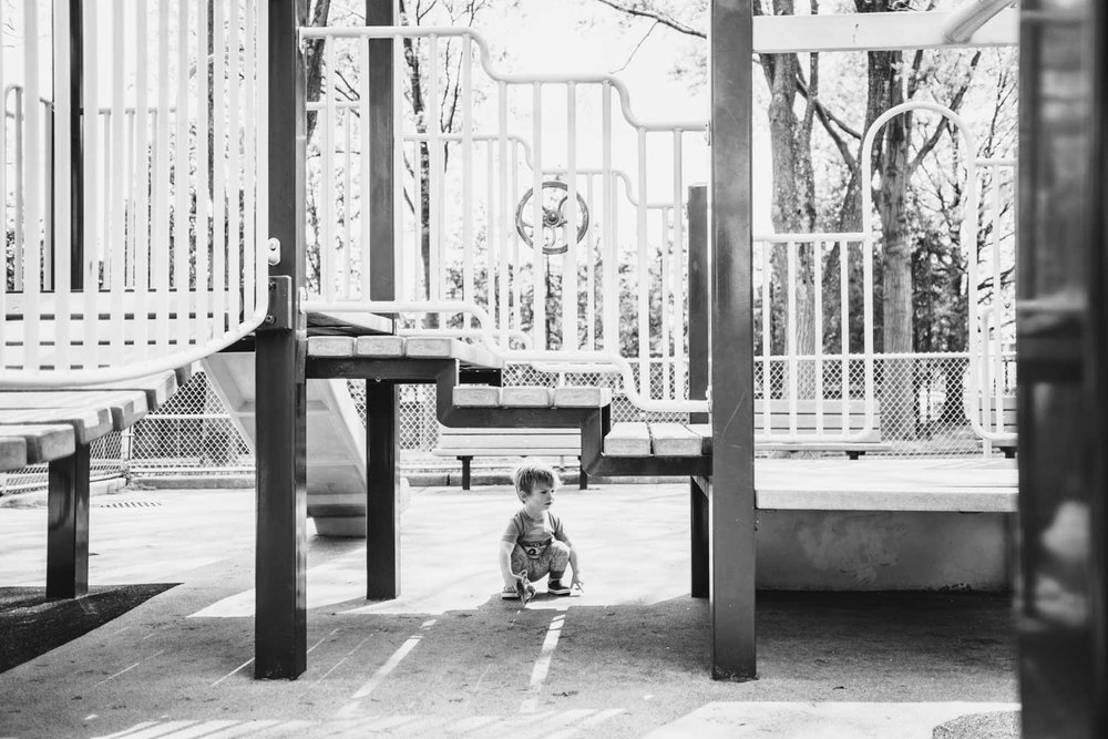 Little boy hides under play structure at the playground.