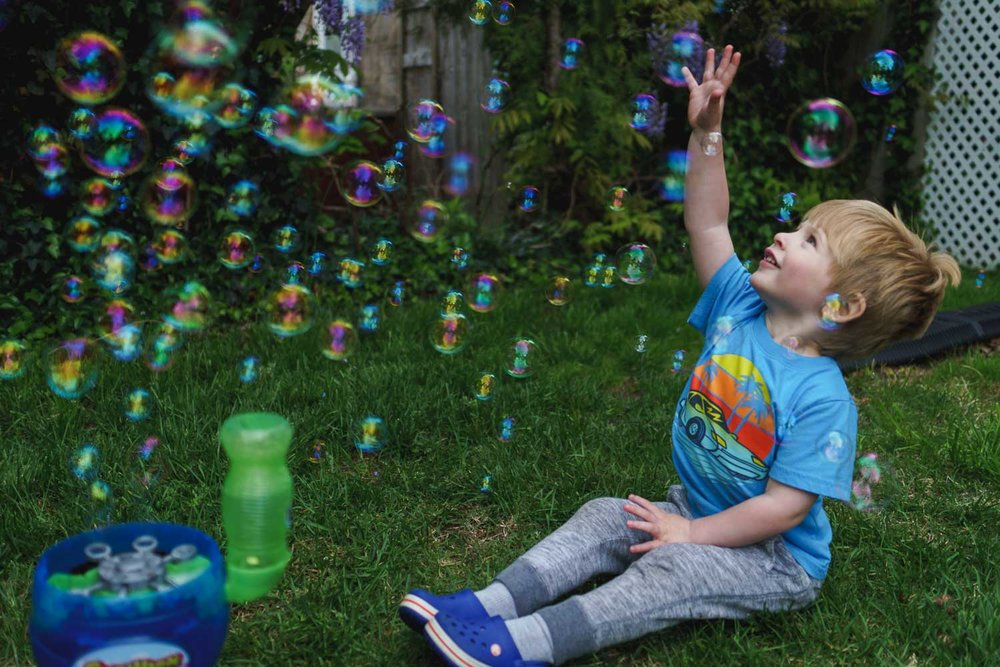 Boy plays with bubble machine on lawn.