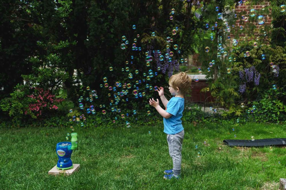 Boy plays with bubbles in the yard.