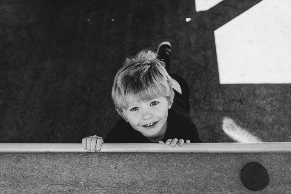 Little boy looking up at the playground.