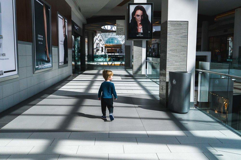 A little boy walks through the mall on a sunny day.