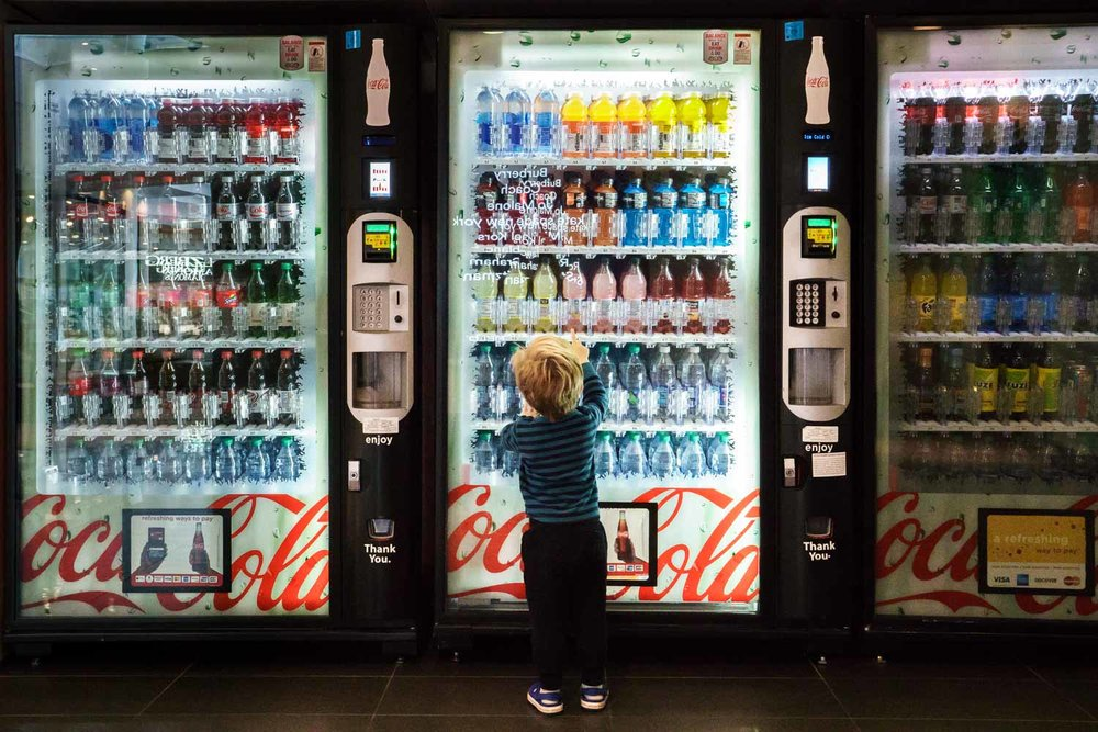 A little boy points at a drink in the vending machine.