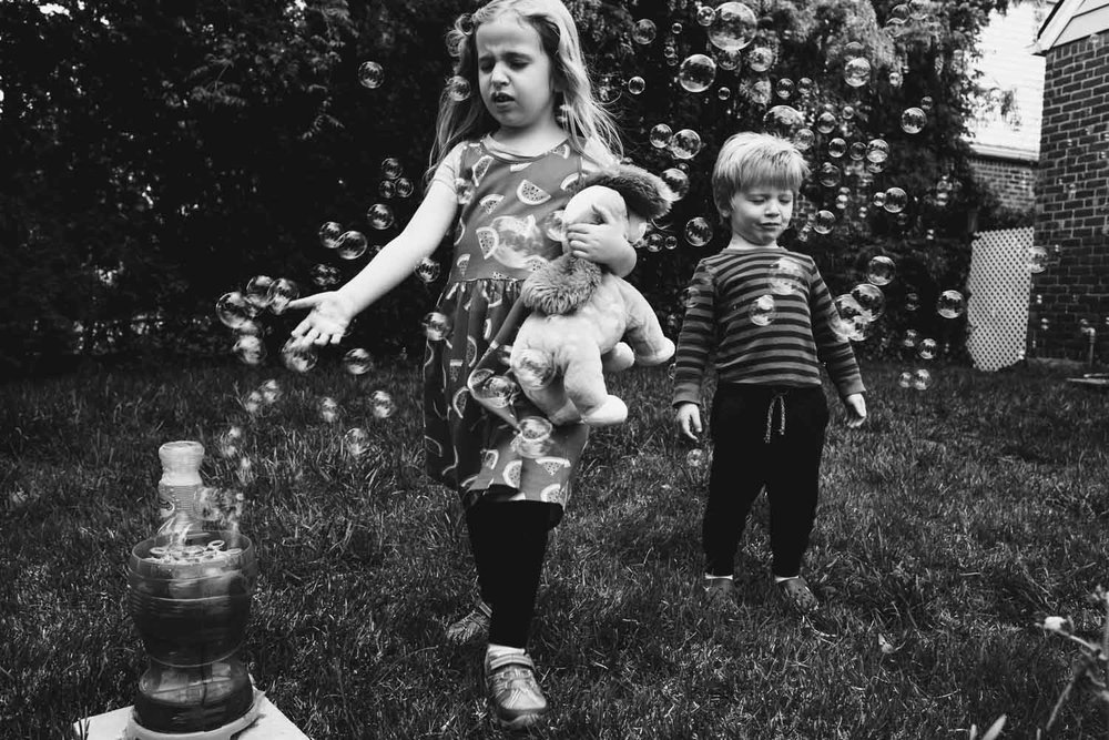 Brother and sister play with bubble machine in front yard.