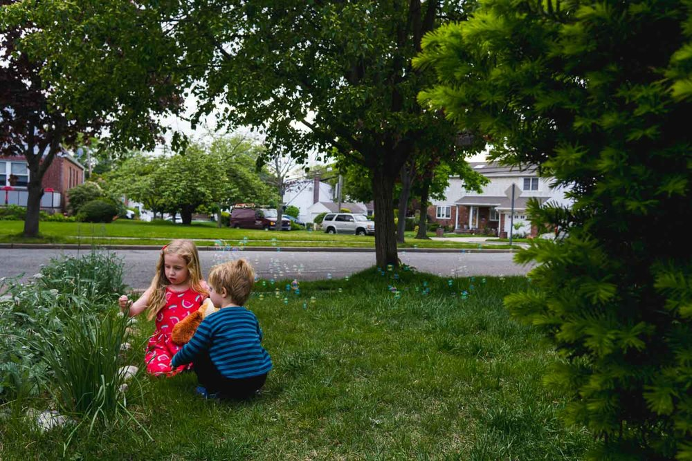 Siblings play on the front lawn.