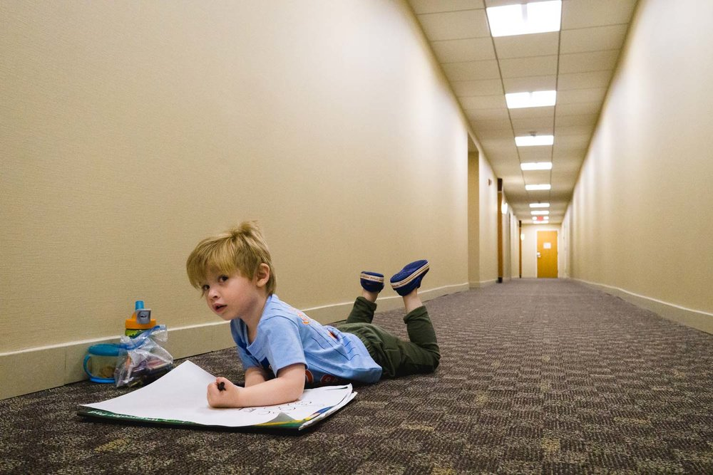 A boy lies in an empty hallway, coloring.