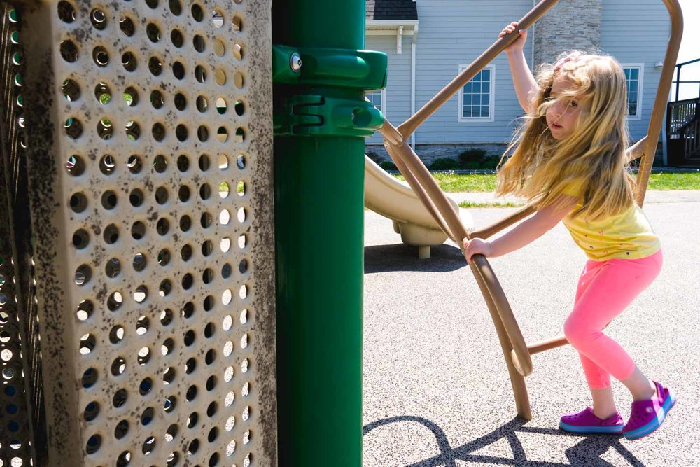 Little girl climbs a playground structure.