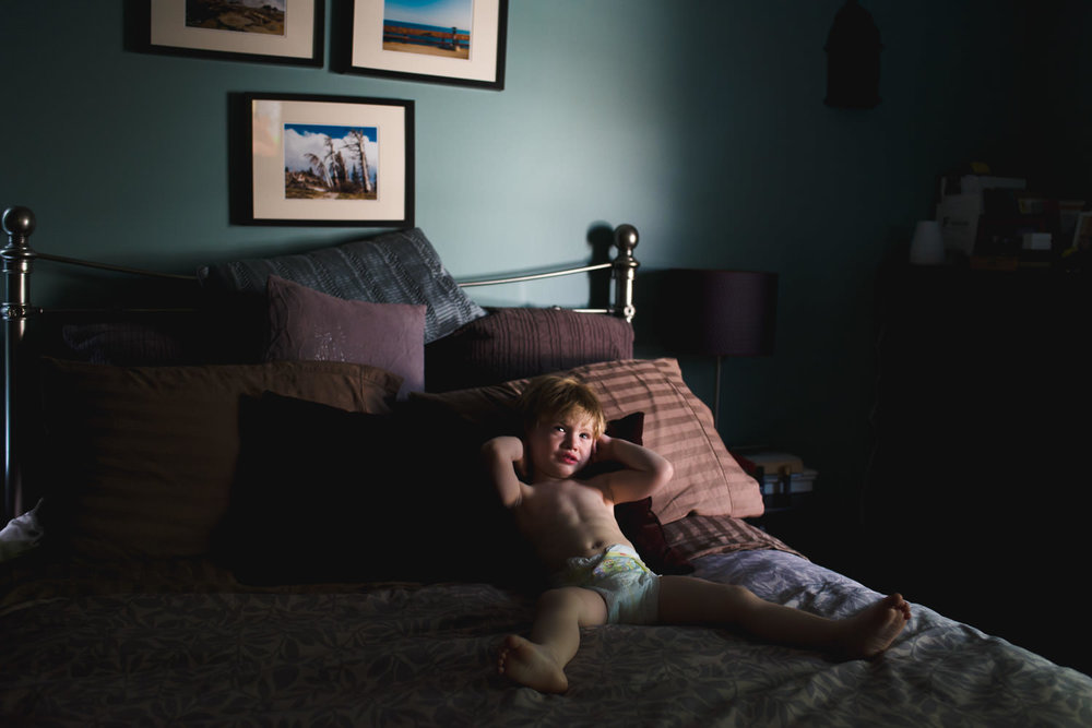 A toddler lies on his parents' bed.