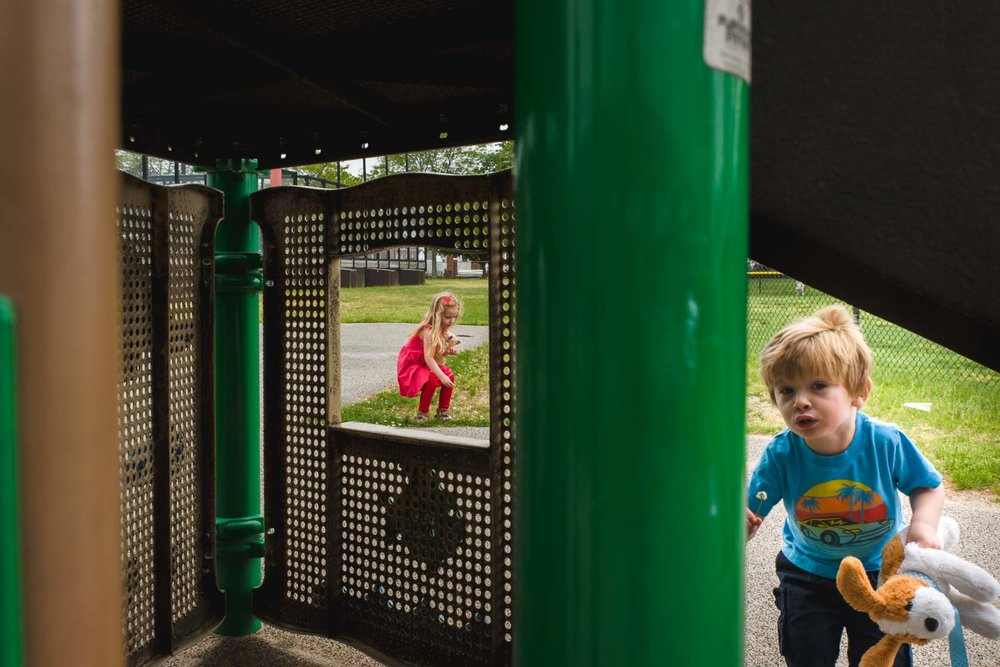 Kids play at the community center under the play structure.