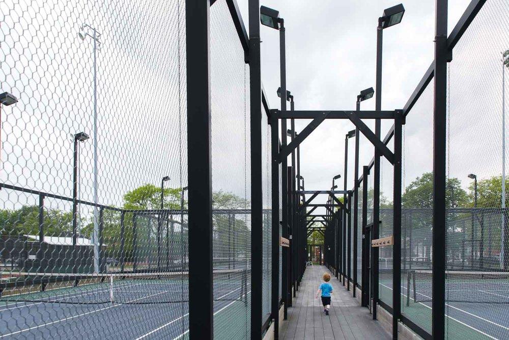 A little boy walks through a tennis court.