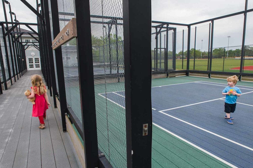 Kids play on the tennis courts at the community center.