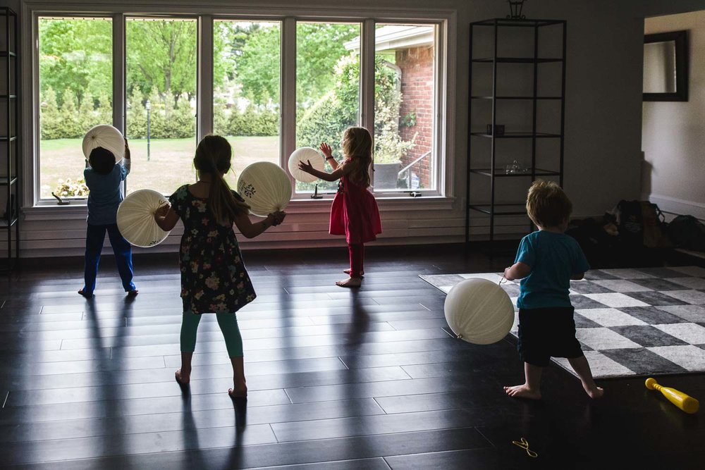 Kids play with big white balloons in a large empty living room.