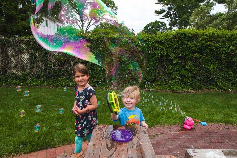 A little boy makes a huge bubble with a bubble gun.