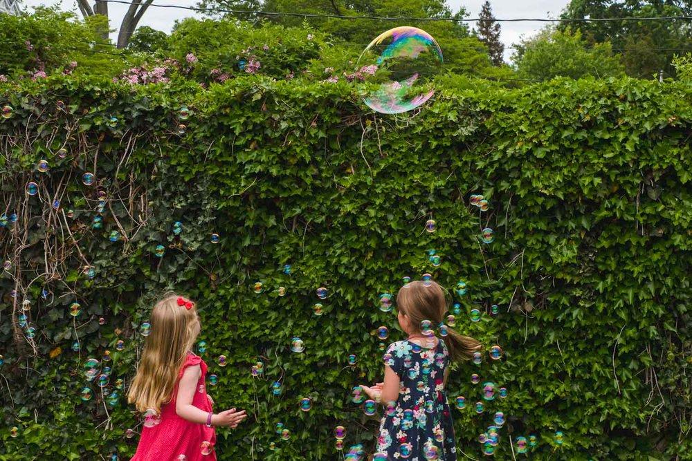 Little girls play in bubbles.