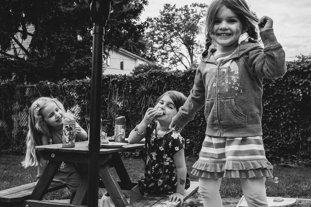 Little girls play together in the backyard.