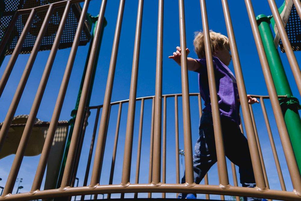 A little boy runs across a bridge on a playground structure.
