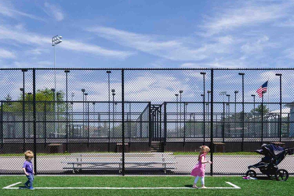 Kids walking on painted line on baseball field.