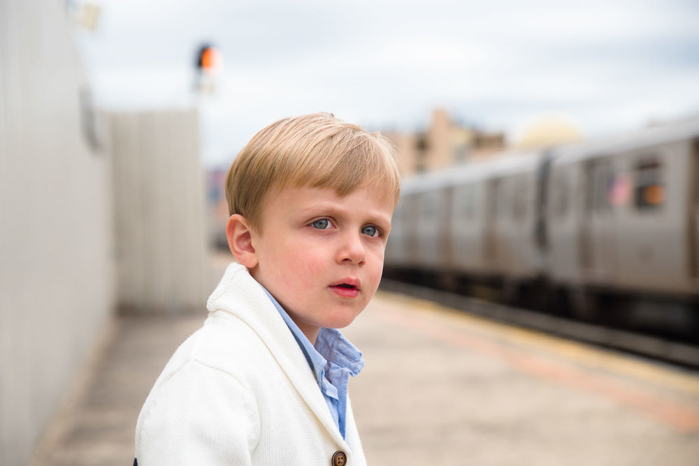 A little boy watches for the subway on the platform.