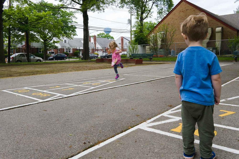 Kids play hopscotch at the playground