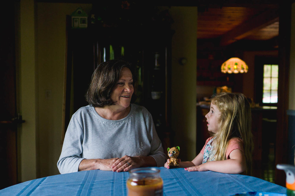 A child and her grandmother talk at the dining room table.